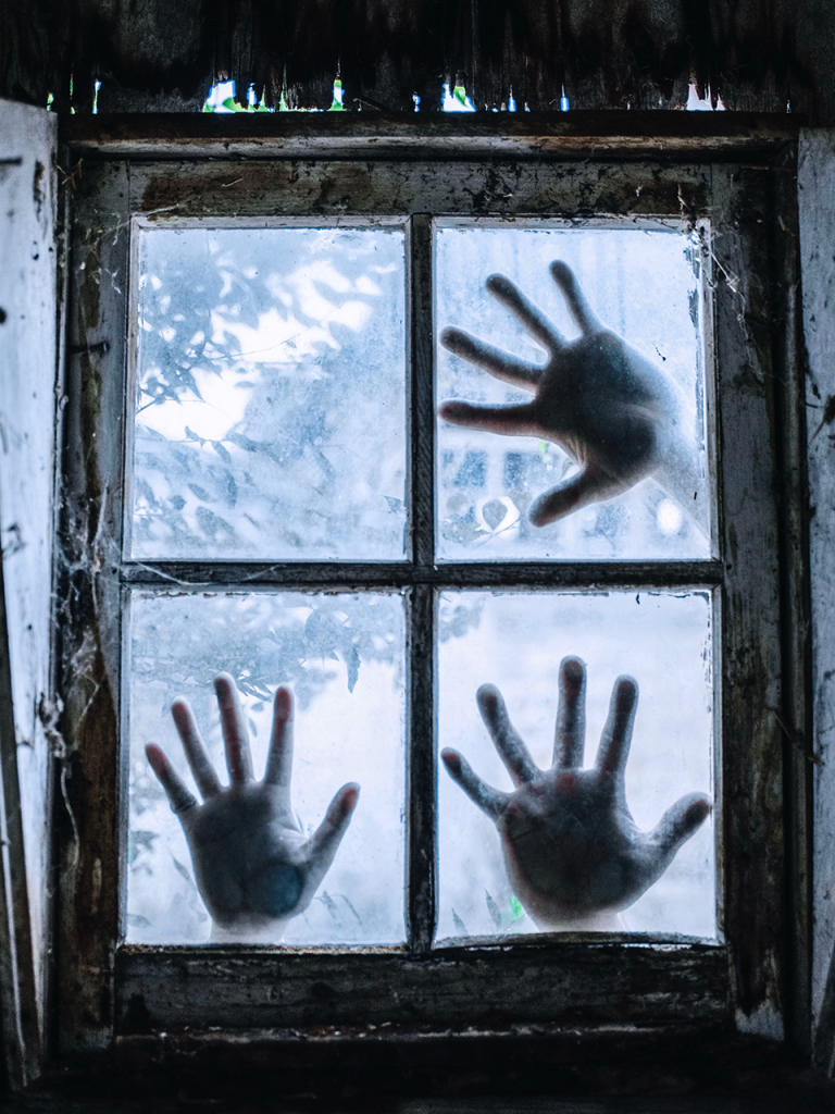 3 hands on frosty old window to use as a creepy photo booth background
