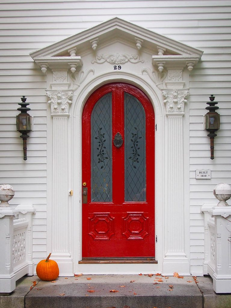 red door on white house with pumpkin on steps photo booth background