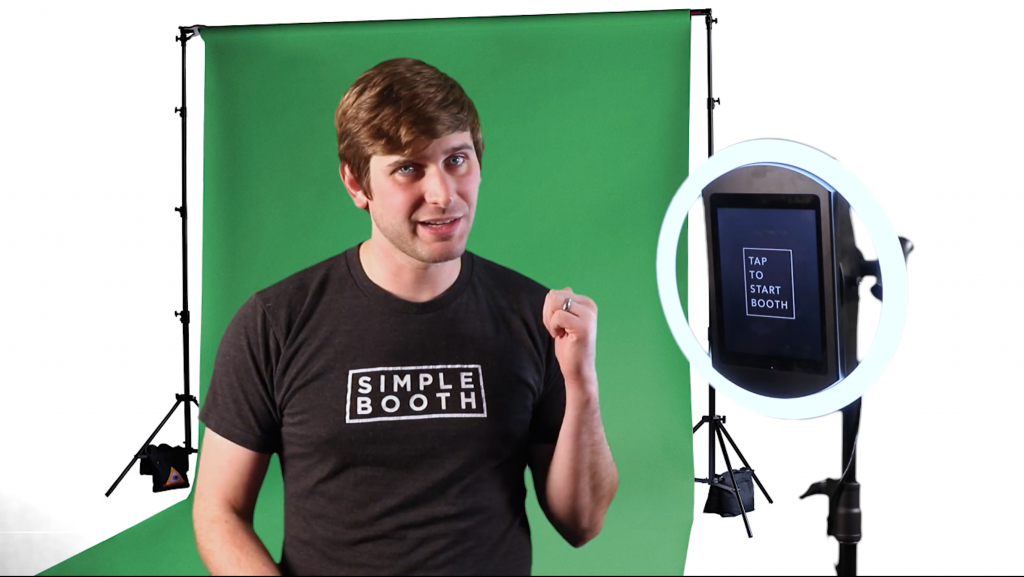 man standing in front of green screen backdrop standing next to simple booth halo photo booth