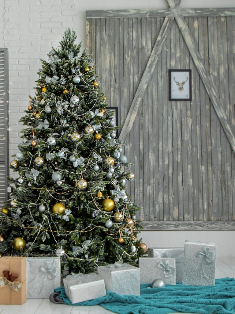 christmas tree and gifts in front of wood wall