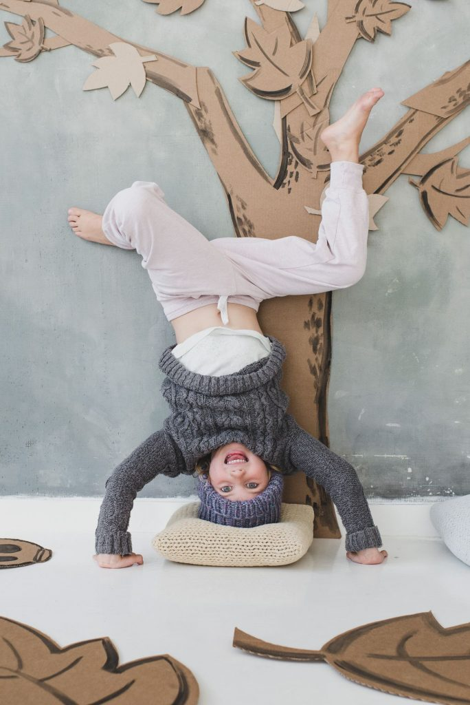 child at home doing headstand in front of photo booth