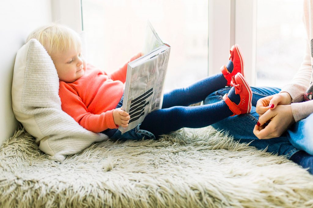 child at home reading book with mother