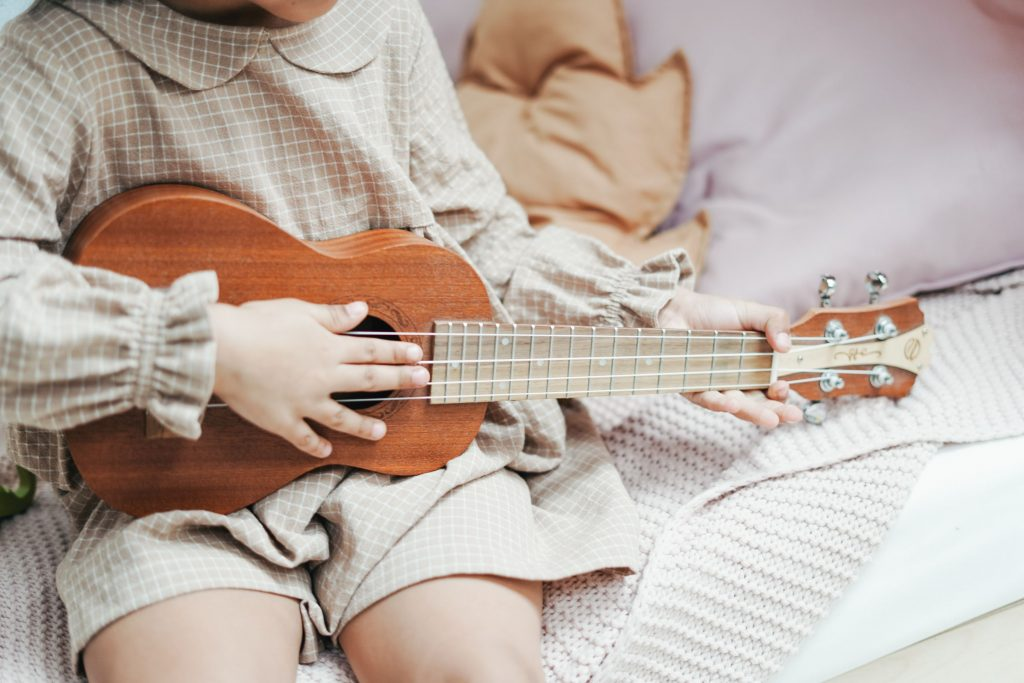 little girl playing ukulele