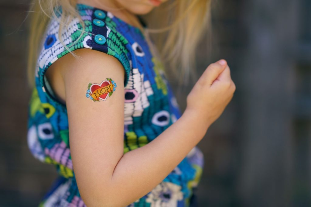 little girl wearing temporary tattoo at home